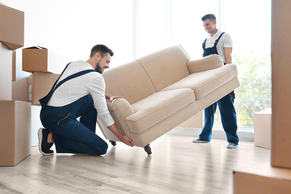Zwei Männer heben ein Sofa